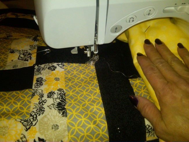 [Here I go quilting the center black first]